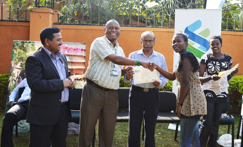 Mr. Herbert Zake, Head of Corporate Affairs at SCB Uganda and Mr. Abul Kashem Mozumder, BRAC Uganda Country Representative, present Kisa with her certificate during the closing ceremony.